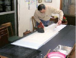 写真(4)取り棒と撫刷毛を使って和紙を貼り合わせる